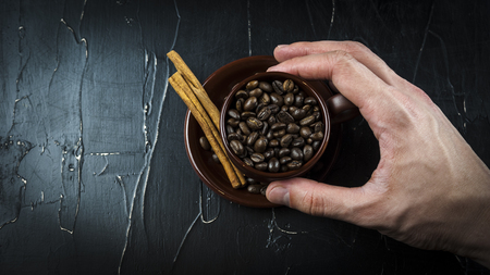 A mans hand holds a cup of coffee beans with cinnamon