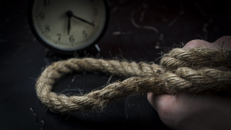 A mans hand holds a rope with a loop with alarm clock, the concept of self-sacrifice 写真素材