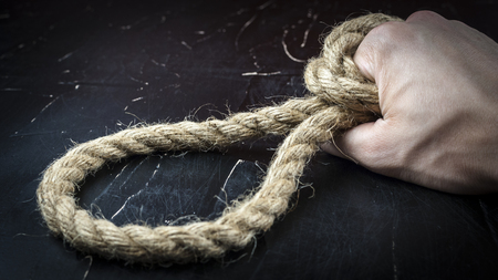 A man's hand holds a rope with a loop, the concept of self-sacrifice Foto de archivo