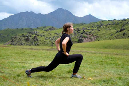 The girl is engaged in yoga in the mountains , people