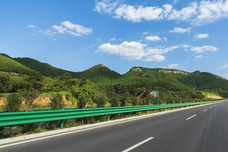 Paisaje de la carretera bajo un cielo azul y nubes blancas Foto de archivo