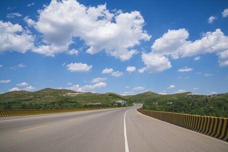 Asphalt road scenery under blue sky and white clouds