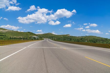 Landscape of mountain town road asphalt road under blue sky and white clouds