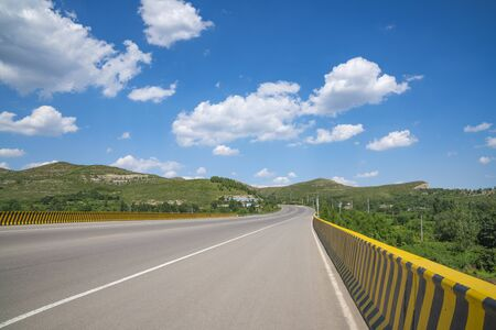 Wide road under blue sky and white clouds