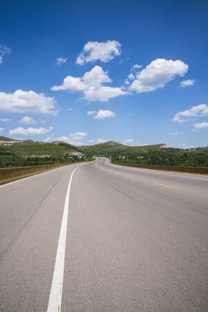 Snelweglandschap onder blauwe lucht en witte wolken