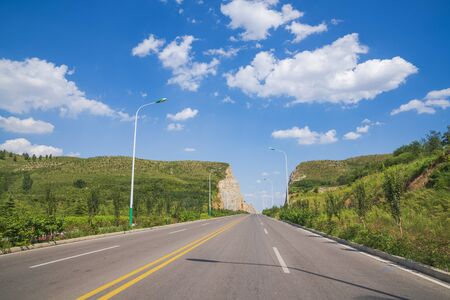 Asphalt road landscape stretches out into the distance under blue sky and white clouds