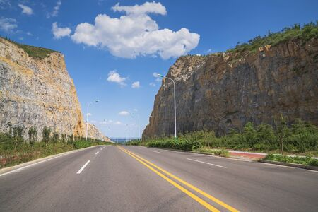 Straight asphalt road through the cliff and stretched out into the distance under the blue sky and white clouds