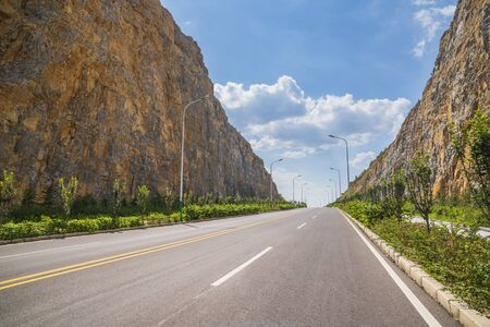 Asphalt road through the cliff and stretched out into the distance under the blue sky and white clouds