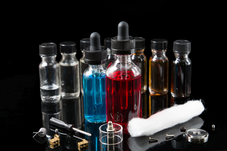 Vaporizer smoke with juice bottles, screwdriver and cotton wick with tools Stock Photo