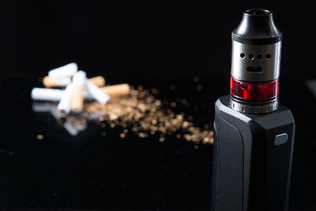 Pile of broken cigarettes with modern electronic cigarette Stock Photo