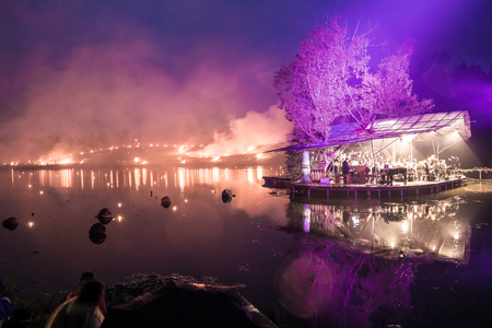 Floating orchestra on a lake with forest fire background