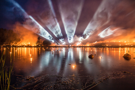 Burning grass with bright light tubes over the lake