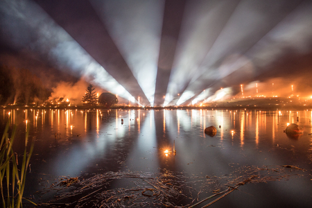 Searchlight show with fire show over a lake at night