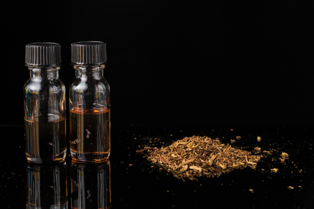E-liquids next to pile of grinded tobacco leaves Stock Photo
