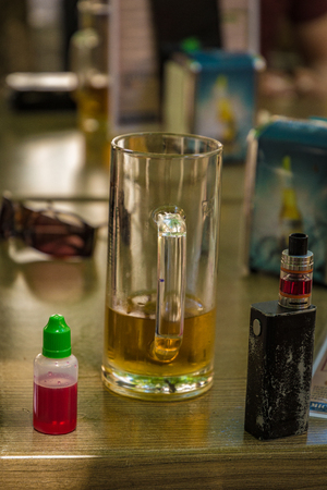 Vaporizer and almost empty beer with bottle and fork on table