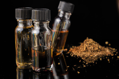 E-liquid bottles next to grinded tobacco leaves Stock Photo