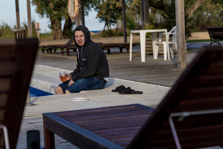 Student in a hoodie drinking beer and tipping legs into pool water Stock Photo