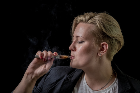 Young adult female inhaling smoke from electronic cigarette Stock Photo