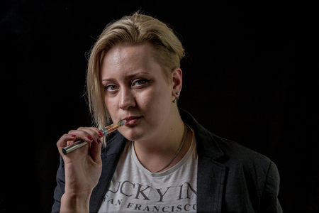 Woman holding electronic cigarette between her teeth