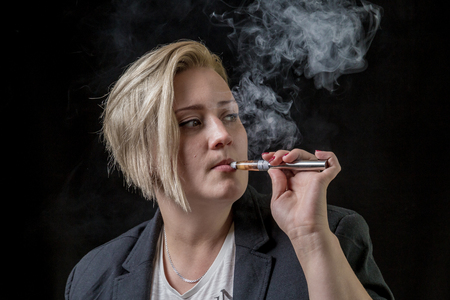 Woman looking on the side while smoking electronic cigarette Stock Photo
