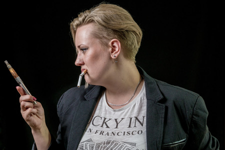 Woman looking at electronic cigarette and is doubting