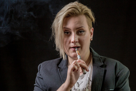Confused and surprised woman holding electronic cigarette between her teeth
