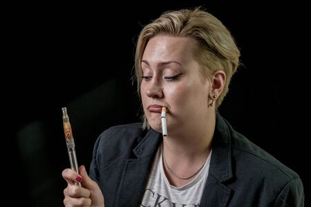 Woman looking at electronic cigarette and thinking about it
