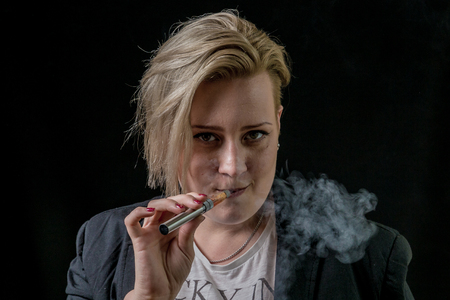 Woman smoking thin electronic cigarette and looking at in the camera