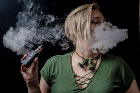 Young adult female exhaling smoke clouds from electronic cigarette Stock Photo