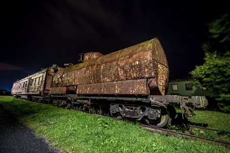 Decayed locomotive car at night