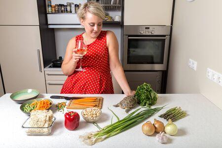 Woman observes tortoise eating on salad Stock Photo