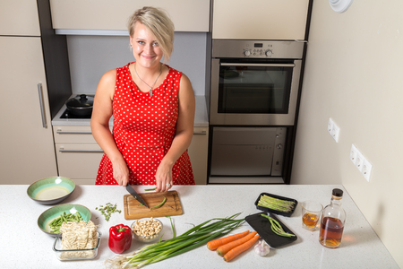 Girl smiling and cutting asparagus Stock Photo - 87636783