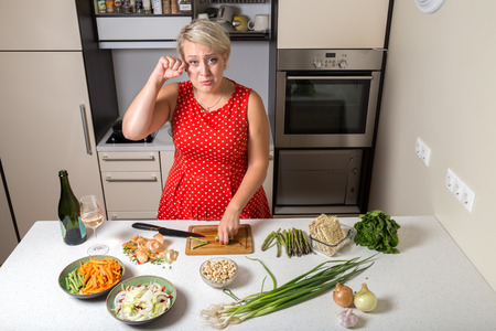 Female in kitchen cutting asparagus and rubbing her eye Stock Photo - 87636788