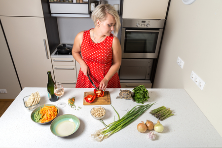 Woman cutting paprika and looking over shoulder of tortoise eating salad Stock Photo - 87636790