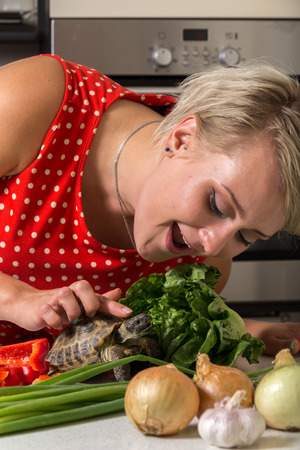 Girl leaning down and petting tortoise on its head next to big roman salad