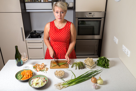 Surprised young woman in kitchen cutting asparagus
