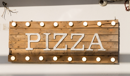 Pizza sign made of wooden planks and light bulbs on top and bottom Stock Photo - 87636798