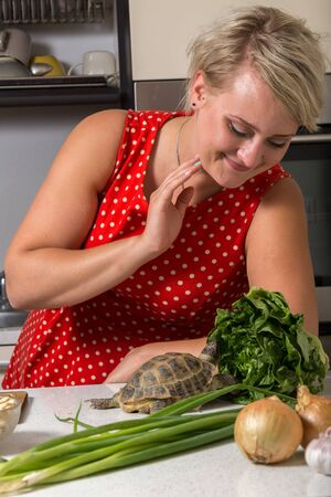 Girl smiles and observes tortoise who is eating