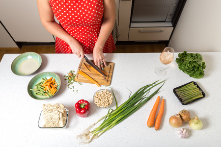 Girl cutting carrots and preparing food Stock Photo