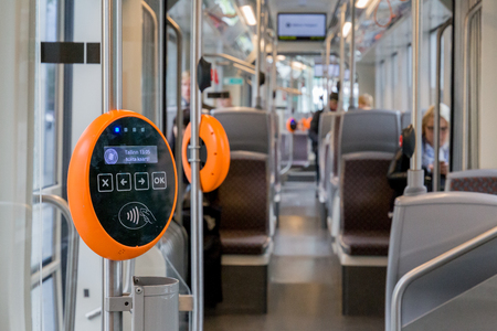 Orange modern magnetic ticket validator with tram and people in background Stock Photo