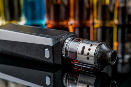 Electronic cigarette on the side with e-juice bottles in the background