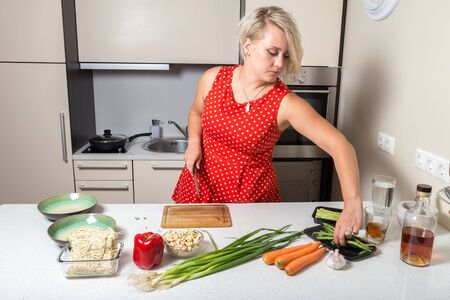 Girl reaching for asparagus and holding knife in other hand