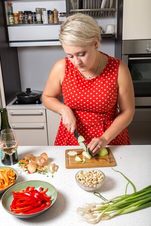 Cute girl cutting onions in red dotted dress
