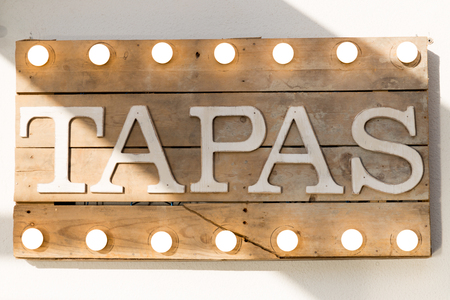Tapas sign made of wooden planks and light bulbs on top and bottom Stock Photo