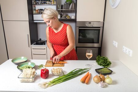 Girl cutting carrot and preparing for vegetable wok Stock Photo