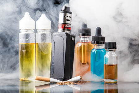 Modern vaporiser versus old tobacco cigarette in smoke cloud Stockfoto