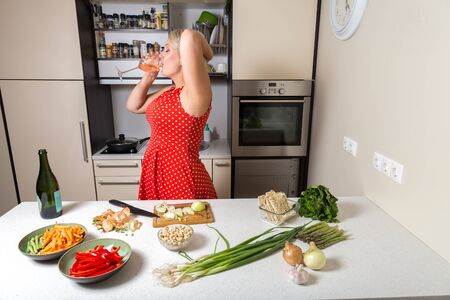 Woman in red dress drinking wine from glass in kitchen Stock Photo