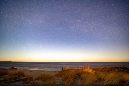 Milky way over sea at night at beach Stock Photo