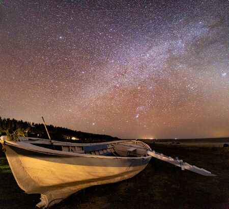 Wooden boat docking on land with milky way at the background