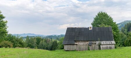 Wooden shed on a green meadow in mountain village.